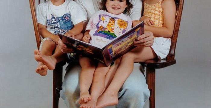 Pai cria cadeira especial para conseguir ler histórias aos três filhos